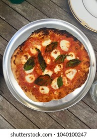 Wood fire pizza Margarita pizza on rustic wooden table outside