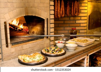 Wood fired pizza oven with pizzas and ingredients for preparation