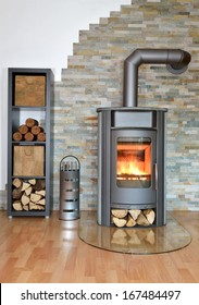 wood fired stove burning with fire-wood. Rack with fire-wood, fire-irons and briquettes in front of brick wall