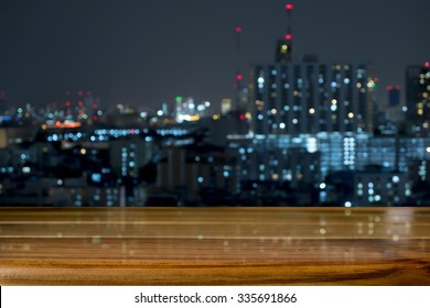 Wood floor with blurred abstract background of city night lights downtown city view : Wooden table with blur background of cityscape