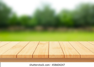 Wood floor with blurred trees of nature park background and summer season, product display montage