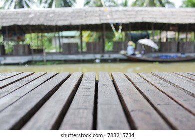 Wood floor with canal and women on the Thai boat in front.