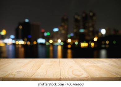 Wood floor (light and panels) with blurred abstract background of city night lights downtown city view and lake. Can be add your product on wood floor: Wooden table with blur background of cityscape.