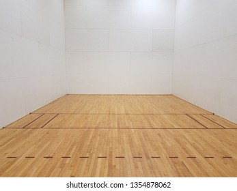 wood floor racquetball court with white walls