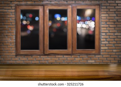 Wood floor or table on wood windows and brick wall with night light of city background use for present product