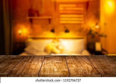 Wood foreground with blur night bedroom for montage display products background.