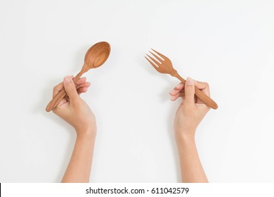 wood fork and spoon in woman hand in top view isolated on white background with clipping path