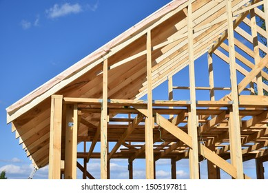 Wood frame residential building under construction.Building construction, wood framing structure at new property development site.new home currently under construction against blue sky.mortgage, loan.