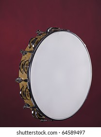 A wood frame tambourine isolated against a red background.