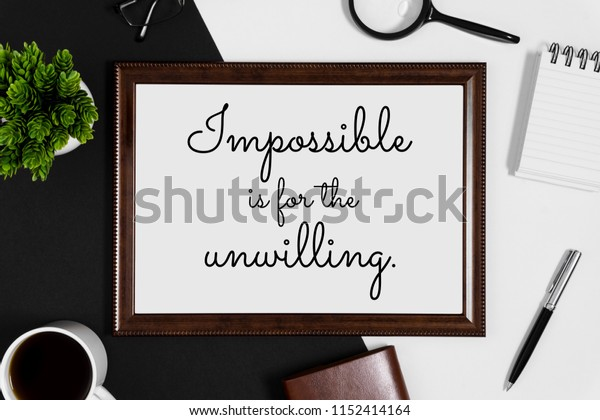 Wood frame with wisdom quote and coffee cup on black and white background.
