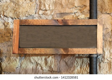 Wood framed chalkboard connected to a vertical pipe in front of textured rock wall.  The chalk area has a blank copy space for you to write your message.