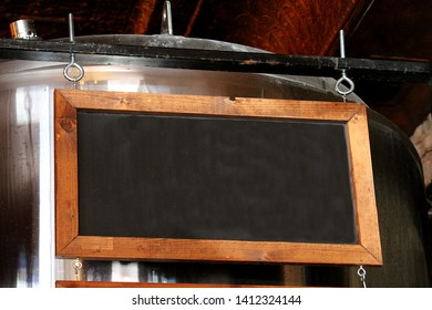 Wood framed chalkboard sign in front of beer brewery vat.  There is blank space on the board for your copy.
