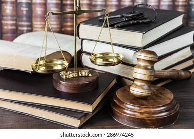 Wood gavel, bunch of keys, scales and stack of old books against the background of a row of antique books bound in leather