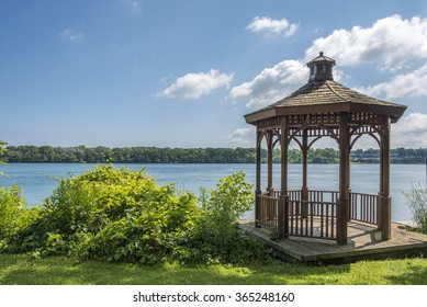 A wood gazebo over looks the Niagara River in Niagara on the Lake, Ontario, Canada on a blue sky day. The United States can be seen in the distance.