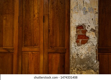 The wood grain wall and the cement pillars are broken