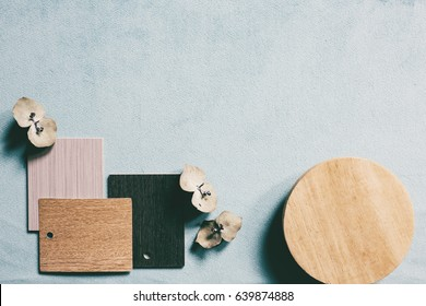Wood, grey and black color scheme on pale blue background mood board
