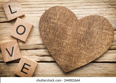 Wood heart on old wooden background - Stock Image. I love you, cast out of wood kubik.