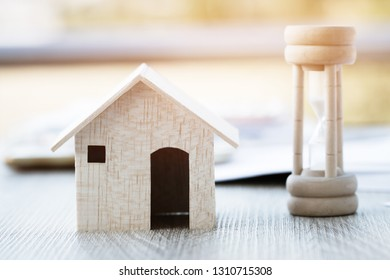 Wood hourglass or sandglass with home. Invertible device with two connected glass bulbs containing sand that takes an hour to pass from upper to lower bulb. Concept for business deadline times