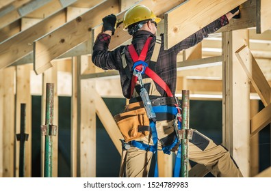 Wood House Frame Construction. Caucasian Carpenter Contractor and His Job. Industrial Theme.