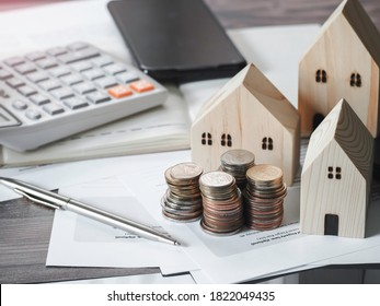 Wood house model coins money with account book finance and banking business finance concept for background.