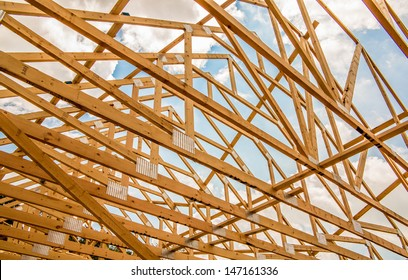 Wood house truss against blue sky with puffy clouds