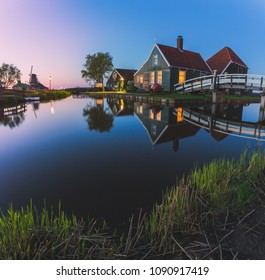 Wood houses and windmill are reflected in the blue water of river Zaan Zaanse Schans North Holland The Netherlands Europe