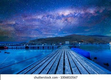 Wood jetty with milkyway background at Wairepo Arm, Twizel, New Zealand