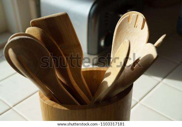 wood kitchen utensils in morning light