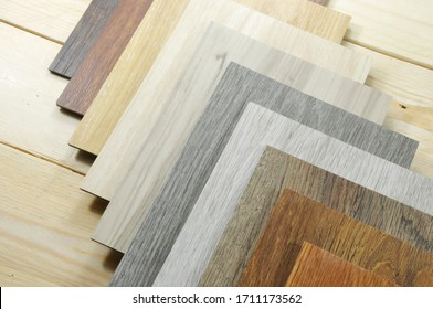 Wood laminate floor. Sample of laminate and vinyl tile on oak wooden background for new construction or renovate building or home. Venner. parquet