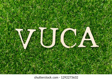 Wood letter block in word (abbreviation of Volatility, uncertainty, complexity and ambiguity) on artificial green grass background