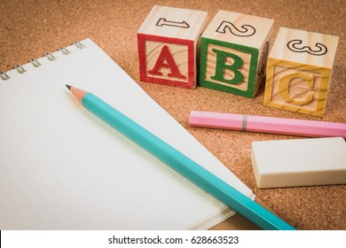Wood letter blocks alphabet ABC with notebook or worksheet for practice alphabet handwriting drill. ABC practice for kids concept.