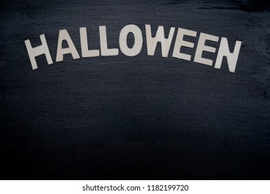 """Wood letter """"HALLOWEEN"""" on black wood background. Holiday season. Party. Can be use for advertising, banner, brochure, web. Free space for text."""