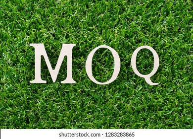 Wood letter in word MOQ (Abbreviation of Minimum Order Quantity) on artificial green grass background