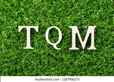 Wood letter in word TQM (Abbreviation of total quality management) on artificial green grass background