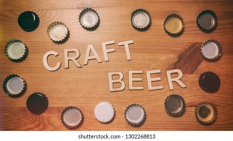 Wood letters spelling out craft beer. Bordered by beer bottle caps.
