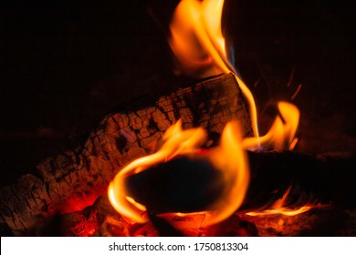 Wood log burning in the chimenea. Fire wood, coal and amber ash closeup. Red tongues of flame and glowing amber. Concept of home and warmth. Close up shot of burning firewood in the fireplace.