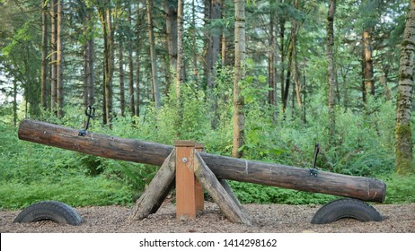 A wood log seesaw teeter totter in a park playground with green forest background.