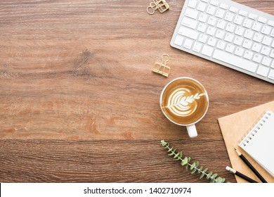 Wood minimalist office desk table with computer keyboard, cup of cafe latte coffee and supplies. Top view with copy space, flat lay, minimal style.