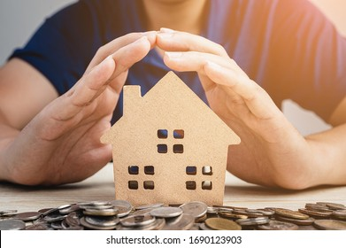 Wood model house on pile of coin is covered by man's hand for protection. Property insurance, real estate investment cocept.