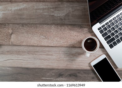 wood office desk with computer and smart phone with coffee