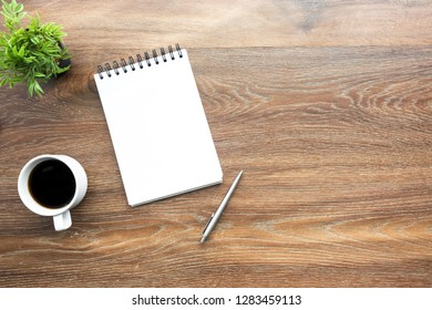 Wood office desk table with blank notebook page with pen and a cup of coffee. Top view with copy space, flat lay.
