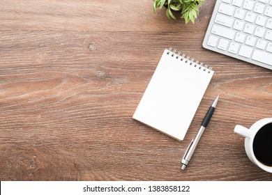 Wood office desk table with blank notebook with pen, cup of coffee and supplies. Top view with copy space, flat lay, internet research concept.