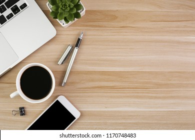 Wood office desk table with laptop, cup of coffee and supplies.