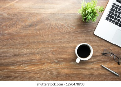 Wood office desk table with laptop, cup of coffee and supplies with morning sun light. Top view with copy space, flat lay.