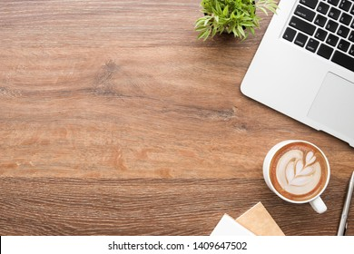 Wood office desk table with laptop computer, cup of latte cofee and notebook with pen. Top view with copy space, flat lay.
