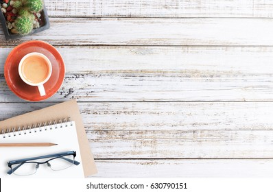 Wood office desk table with notebook, cup of coffee and glasses,flat lay. Top view with copy space (selective focus). Office desk table concept.