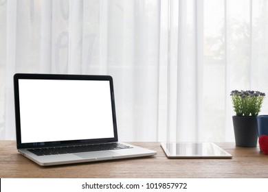 wood office table with blank screen for text  laptop, notebook, smartphone, tablet, cell phone and violet flower pot on white curtain window background, view from front office table. workplace at home
