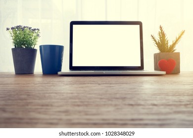 Wood office table with blank screen for text on laptop, blue coffee cup and beautiful flower pot on white curtain windows background. view from front office table.