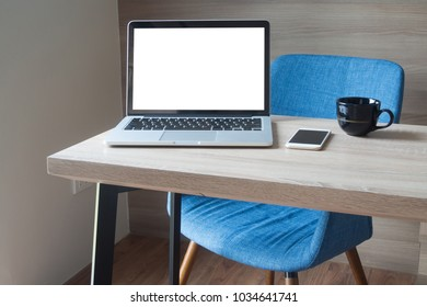 wood office table with blank screen laptop, notebook, blue modern chair and black coffee cup in living room, view from front table. concept of workplace at home.
