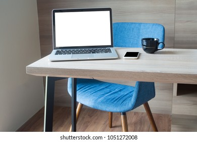 wood office table with blank screen laptop, notebook, smart phone, blue modern chair and black coffee cup in living room, view from front table. concept of workplace at home.